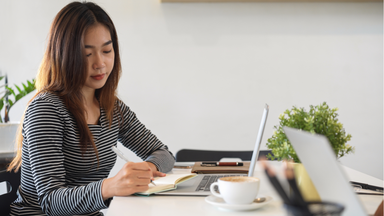 Women working at laptop with notebook and coffee