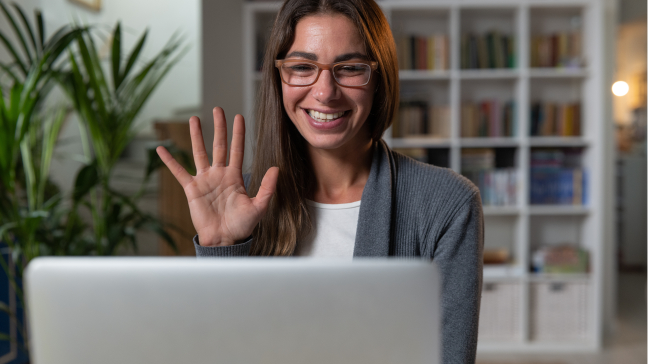Woman with glasses waving and smile to someone on laptop screen